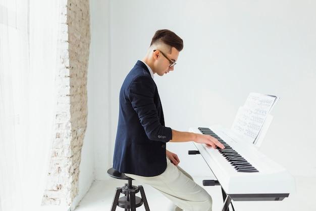 Jovem bonito praticando teclado de piano
