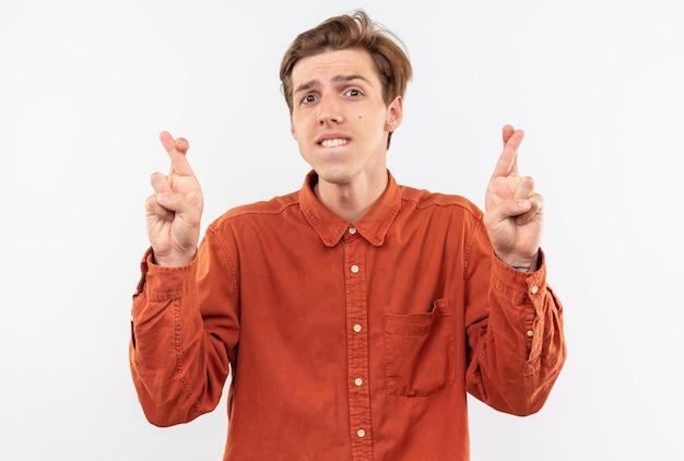 Jovem bonito preocupado com uma camisa vermelha cruzando os dedos