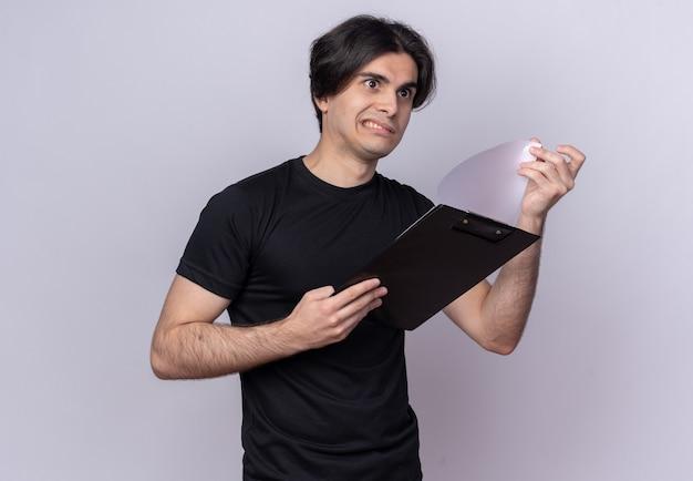 Jovem bonito preocupado com uma camiseta preta folheando a prancheta isolada na parede branca