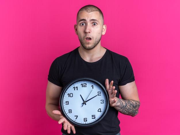 Jovem bonito preocupado com uma camiseta preta segurando um relógio de parede isolado no fundo rosa