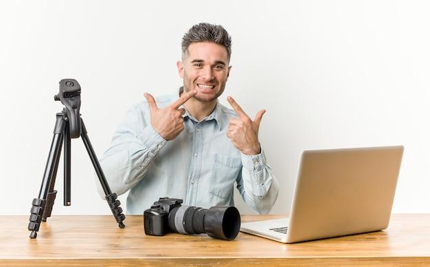 Jovem bonito professor de fotografia sorri, apontando o dedo para a boca.