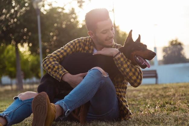 Jovem bonito que brinca com o cachorro no parque.