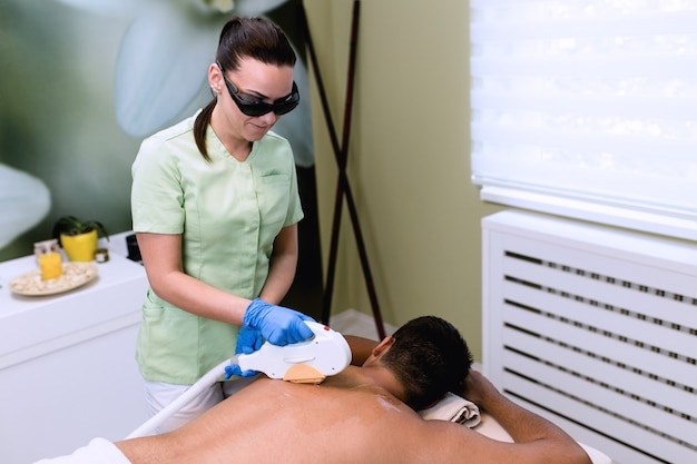 Jovem bonito recebendo procedimento de cosmetologia de remoção de cabelo na clínica de spa de beleza cosmética.
