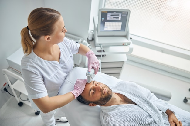 Jovem bonito recebendo tratamento facial a laser em clínica de cosmetologia