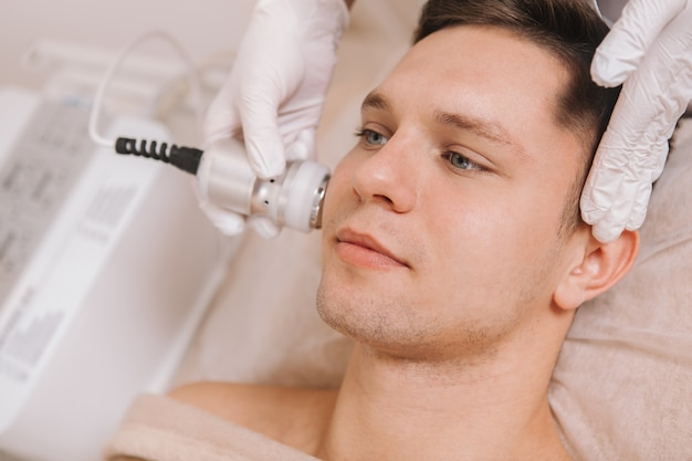 Jovem bonito recebendo tratamento para a pele no salão de beleza
