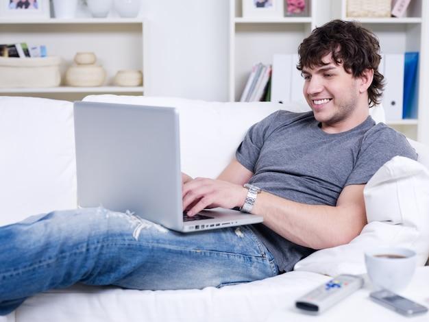 Jovem bonito relaxando usando laptop e deitado no sofá