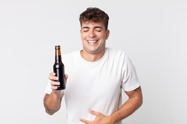 Jovem bonito rindo alto de uma piada hilária e segurando uma garrafa de cerveja