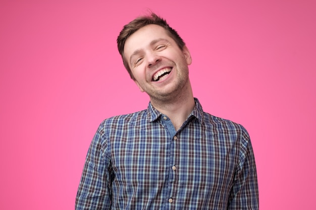 Jovem bonito rindo em fundo rosa