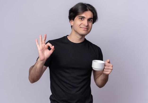 Jovem bonito satisfeito com uma camiseta preta segurando uma xícara de café e mostrando um gesto de ok isolado na parede branca