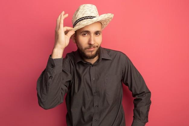 Jovem bonito satisfeito, vestindo camiseta preta e chapéu, segurando um chapéu isolado em rosa