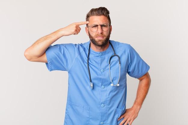 Jovem bonito se sentindo confuso e perplexo, mostrando que você é louco. conceito de enfermeira