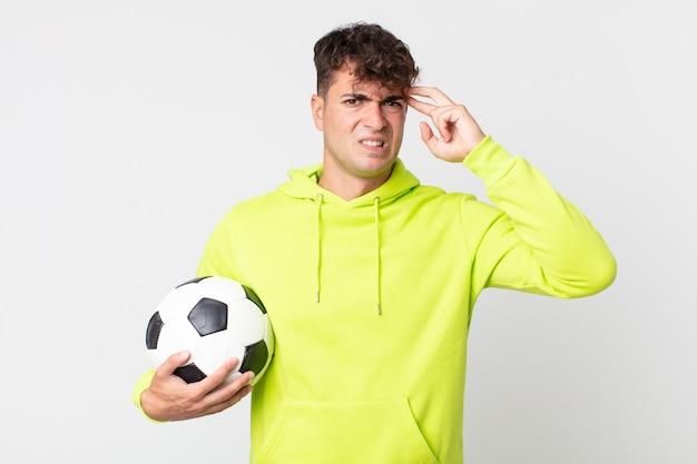 Jovem bonito se sentindo confuso e perplexo, mostrando que você é louco e segurando uma bola de futebol