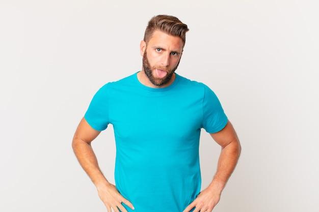 Jovem bonito se sentindo enojado e irritado e com a língua de fora. conceito de fitness