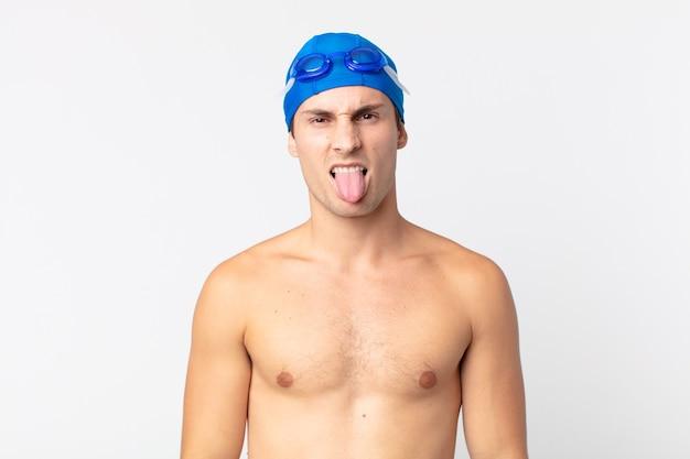 Jovem bonito se sentindo enojado e irritado e com a língua de fora. conceito de nadador