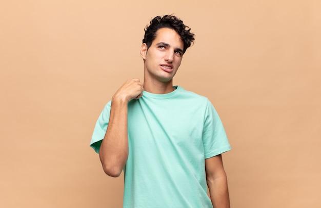 Jovem bonito se sentindo estressado, ansioso, cansado e frustrado, puxando o pescoço da camisa, parecendo frustrado com o problema