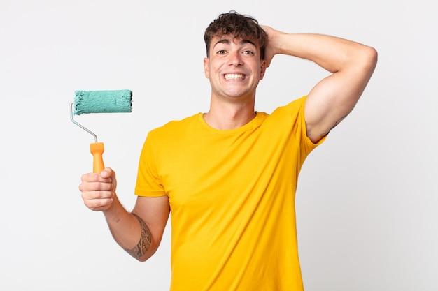 Jovem bonito se sentindo estressado, ansioso ou com medo, com as mãos na cabeça. conceito de pintura de casa