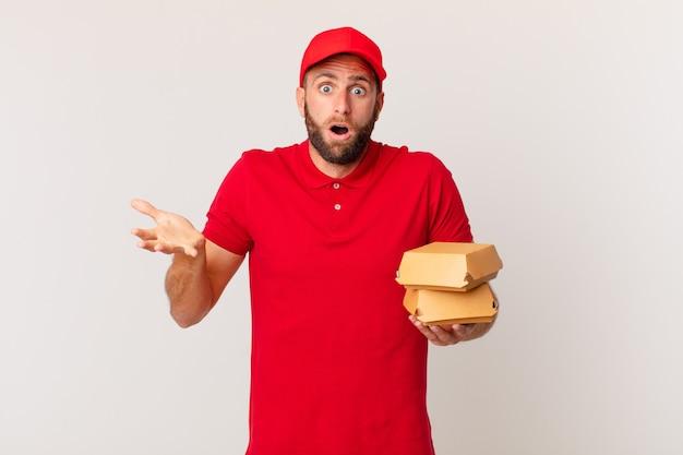 Jovem bonito se sentindo extremamente chocado e surpreso com hambúrguer