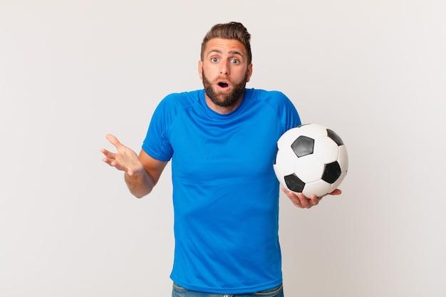 Jovem bonito se sentindo extremamente chocado e surpreso. conceito de futebol