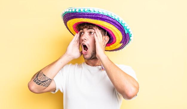 Jovem bonito se sentindo feliz, animado e surpreso. conceito de chapéu mexicano