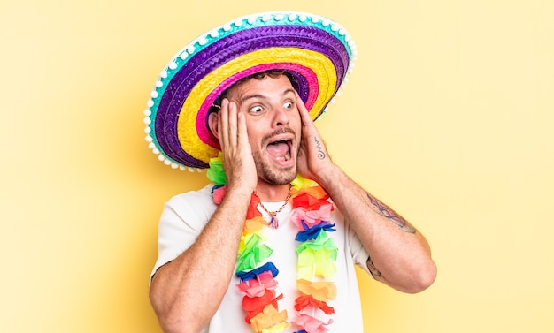 Jovem bonito se sentindo feliz, animado e surpreso. conceito de festa mexicana