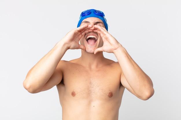 Jovem bonito se sentindo feliz, dando um grande grito com as mãos perto da boca. conceito de nadador