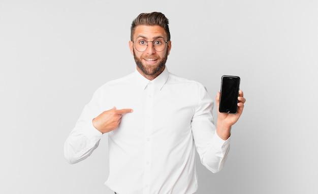 Jovem bonito se sentindo feliz e apontando para si mesmo com um animado e segurando um celular