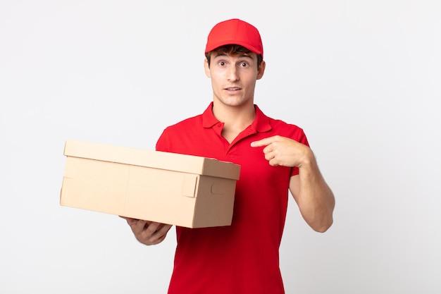 Jovem bonito se sentindo feliz e apontando para si mesmo com um conceito de serviço de pacote de entrega animado.