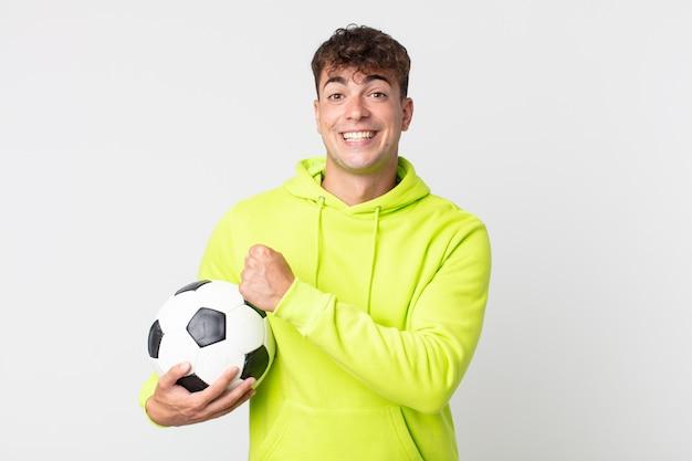 Jovem bonito se sentindo feliz e enfrentando um desafio ou comemorando e segurando uma bola de futebol