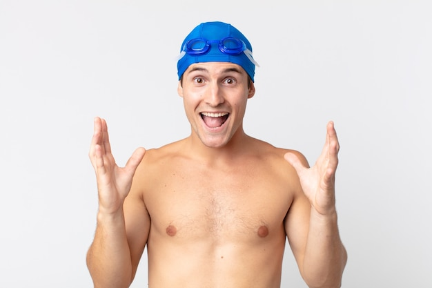 Jovem bonito se sentindo feliz e surpreso com algo inacreditável. conceito de nadador