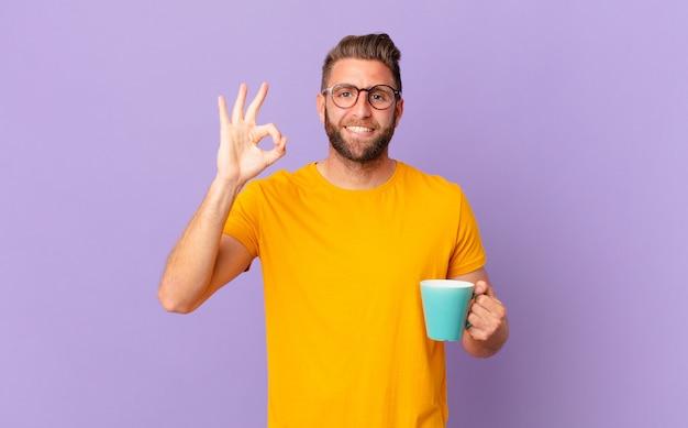 Jovem bonito se sentindo feliz, mostrando aprovação com um gesto certo. e segurando uma caneca de café