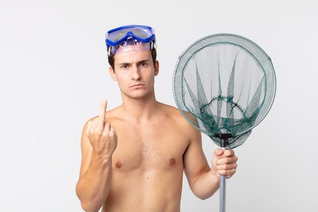 Jovem bonito se sentindo irritado, irritado, rebelde e agressivo com óculos de proteção e uma rede de pesca