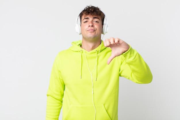 Jovem bonito se sentindo mal, mostrando os polegares para baixo e fones de ouvido