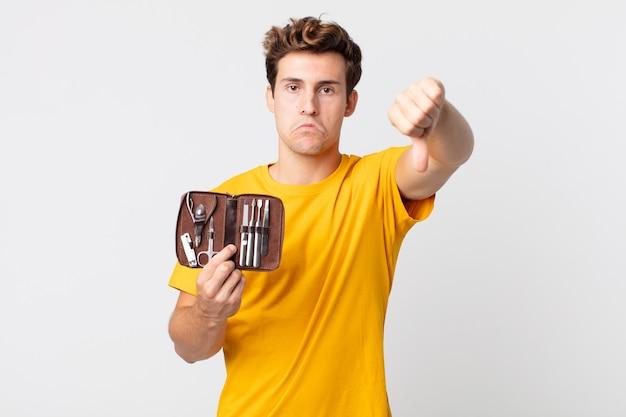 Jovem bonito se sentindo mal, mostrando os polegares para baixo e segurando uma caixa de ferramentas de pregos