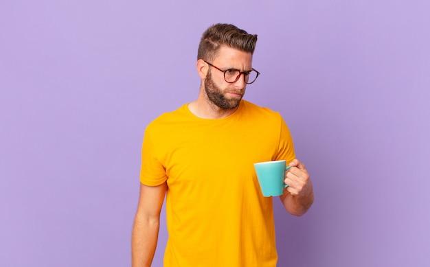 Jovem bonito se sentindo triste, chateado ou com raiva e olhando para o lado. e segurando uma caneca de café