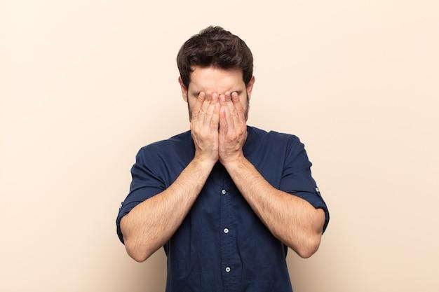 Jovem bonito se sentindo triste, frustrado, nervoso e deprimido, cobrindo o rosto com as duas mãos, chorando