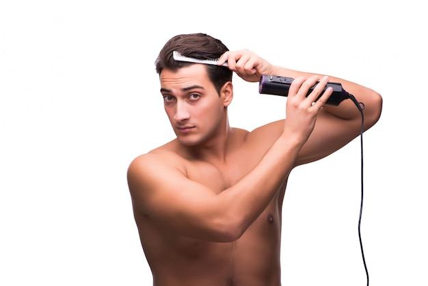 Jovem bonito secando seu cabelo isolado no branco