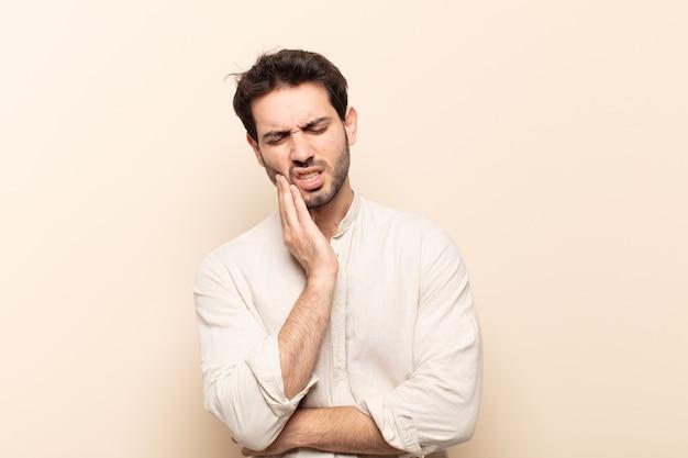 Jovem bonito segurando a bochecha e sofrendo de uma dor de dente dolorida, sentindo-se doente, miserável e infeliz, procurando um dentista
