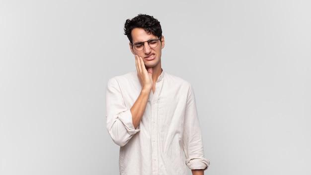 Jovem bonito segurando a bochecha e sofrendo de uma forte dor de dente, sentindo-se doente, miserável e infeliz, procurando um dentista