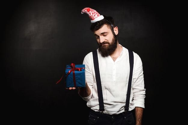 Jovem bonito segurando a caixa de presente de natal sobre preto.