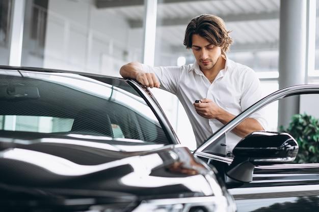 Jovem bonito segurando as chaves em uma sala de exposições de carros