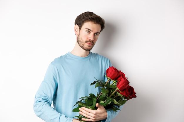 Jovem bonito segurando lindas rosas vermelhas para sua amante no dia dos namorados, parecendo pensativo, em pé sobre um fundo branco