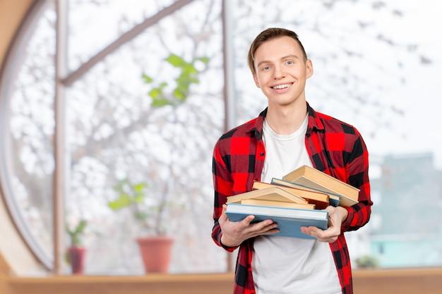 Jovem bonito segurando livros