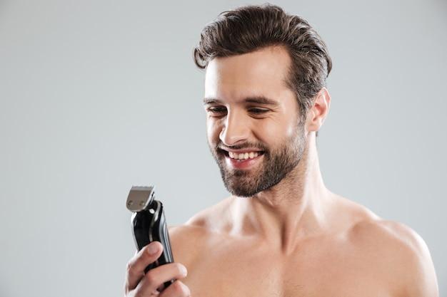 Jovem bonito segurando o barbeador elétrico