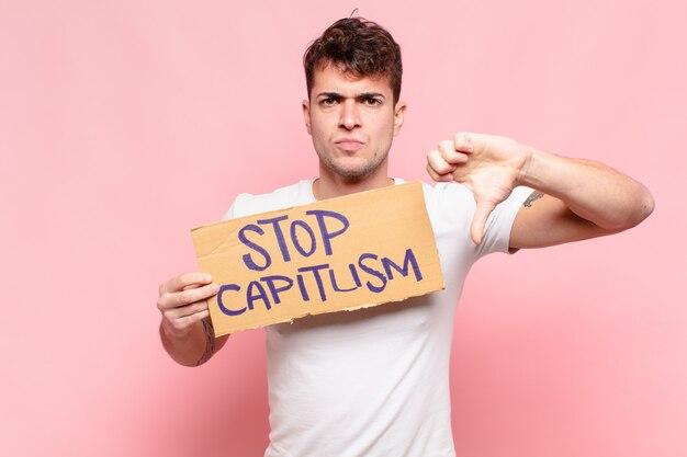 Jovem bonito segurando o capitalismo de parada e dando o polegar para baixo