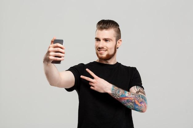 Jovem bonito segurando o telefone fazendo selfie muro cinza.