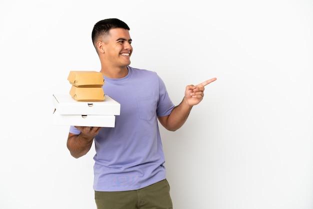 Jovem bonito segurando pizzas e hambúrgueres sobre um fundo branco isolado, apontando o dedo para o lado e apresentando um produto
