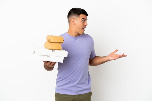 Jovem bonito segurando pizzas e hambúrgueres sobre um fundo branco isolado com expressão de surpresa enquanto olha para o lado
