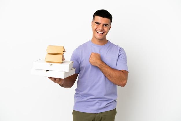 Jovem bonito segurando pizzas e hambúrgueres sobre um fundo branco isolado, comemorando uma vitória