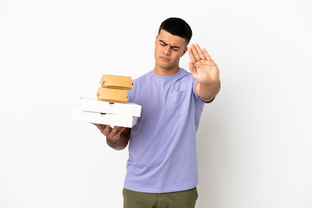 Jovem bonito segurando pizzas e hambúrgueres sobre um fundo branco isolado, fazendo um gesto de pare e desapontado