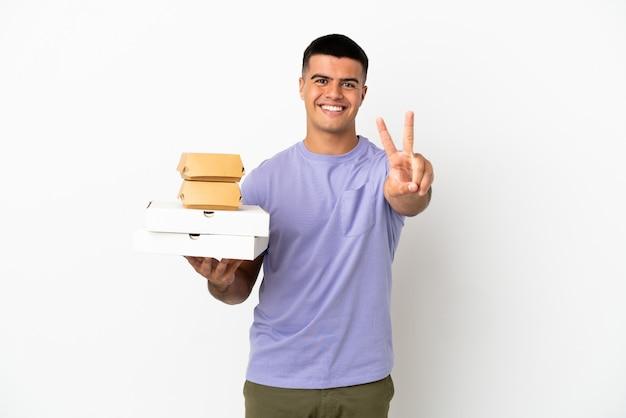 Jovem bonito segurando pizzas e hambúrgueres sobre um fundo branco isolado, sorrindo e mostrando o sinal da vitória